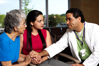 Photo of doctor reaching out to older woman and daughter