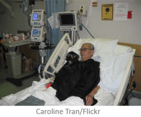 photo of elderly man in hospital bed with medical equipment