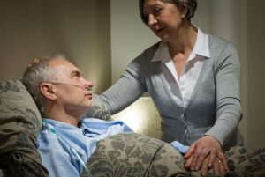 photo woman taking care of sick old man in bed - concerns for patieent hand-offs