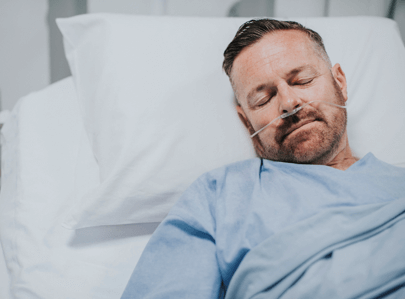 man sleeping in hospital bed