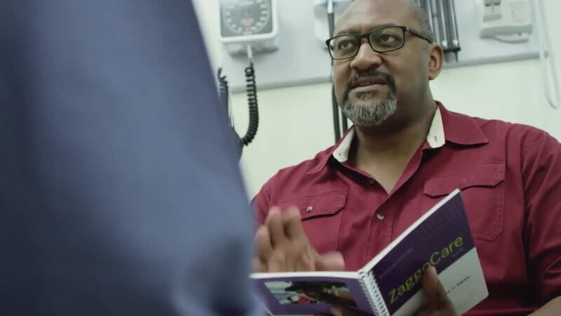 A man reads the ZaggoGuide while speaking with a doctor - the ZaggoCare System helps patients and family caregivers navigate the medical world