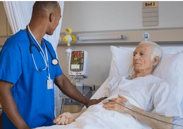photo elderly man in hospital bed, speaking with doctor - Tips to Better Manage a Chronic Disease