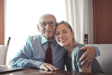 photo older man with granddaughter seated at a table - get paid as a family caregiver