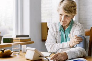 photo older woman taking her blood pressure at home