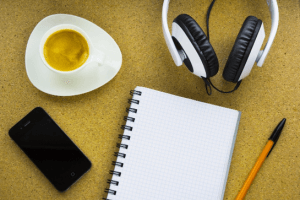 photo of headphones, notebook, phone and pen on a table